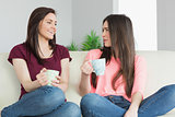 Two girls sitting on a sofa looking each other and drinking a beverage