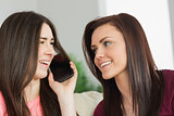 Two happy girls calling someone with a mobile phone