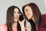 Two cheerful girls calling someone with a mobile phone