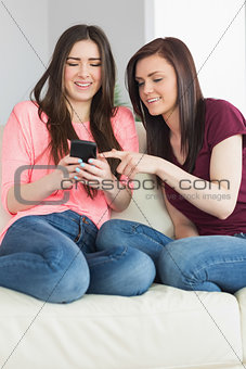 Two smiling girls sitting on a sofa looking at a mobile phone