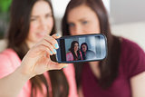 Two smiling girls sitting on a sofa taking a photo of themselves with a mobile phone