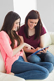 Two smiling girls sitting on a sofa using a tablet pc