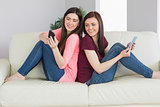 Two smiling girls sitting on a sofa using tablet pc and mobile phone