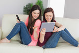 Two happy girls sitting on a sofa using tablet pc and mobile phone