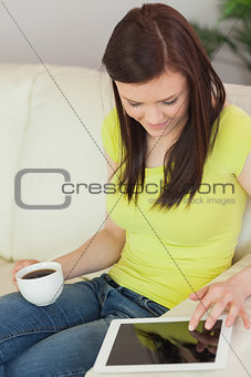 Smiling girl sitting on a sofa using a tablet pc and holding a cup of coffee