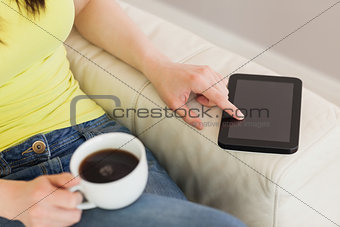 Girl using a tablet pc and holding a cup of coffee