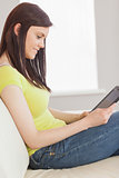 Pretty girl sitting on a sofa using a tablet pc