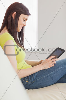 Happy girl sitting on a sofa using a tablet pc