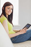 Cheerful girl sitting on a sofa using a tablet pc