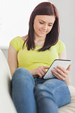 Content girl sitting on a sofa using a tablet pc