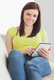 Relaxed girl sitting on a sofa using a tablet pc
