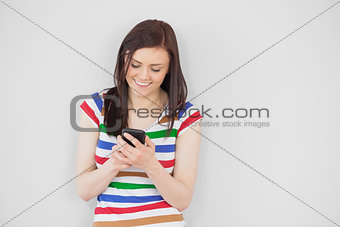 Smiling girl using her mobile phone