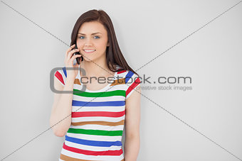 Smiling girl calling with her mobile phone looking at camera