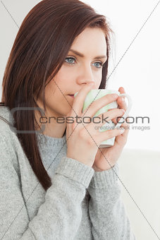 Thinking girl drinking a cup of coffee