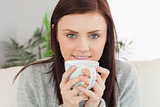 Smiling girl drinking a cup of coffee