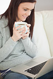 Relaxed girl sitting on a sofa holding a cup of coffee and looking a laptop