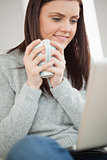 Smiling girl sitting on a sofa holding a cup of coffee and looking at laptop