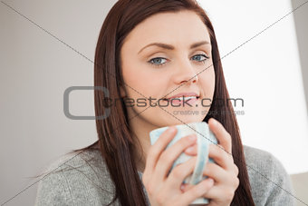 Thoughtful girl holding a cup of coffee and looking at camera