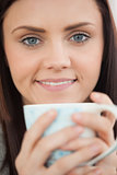 Smiling girl holding a cup of coffee