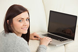 Smiling girl using a laptop on a sofa looking at camera