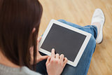 Girl using a tablet pc sitting on the floor