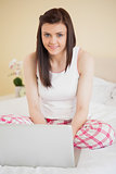 Smiling girl using a laptop sitting on her bed looking at camera