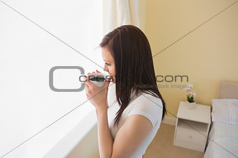 Girl drinking a cup of coffee in a bedroom