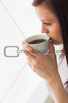 Thoughtful teen holding a cup of coffee looking away