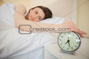 Awakened girl turning off her alarm clock