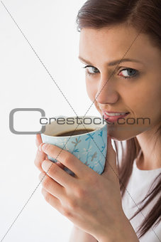 Thoughtful girl looking at camera and drinking a cup of coffee