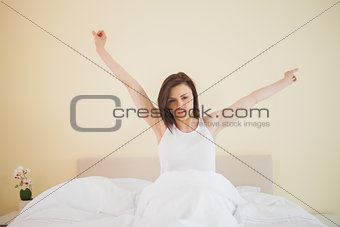 Awakened girl stretching in her bed