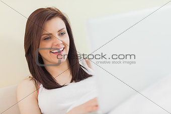 Laughing girl looking and using a laptop lying on a bed