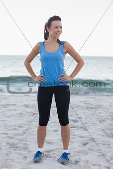 Brunette woman wearing sport wear in front of ocean