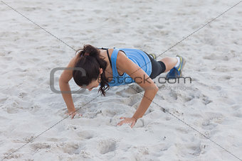 Woman doing push ups at beach