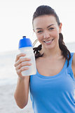 Smiling woman showing her water bottle