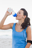 Woman drinking bottled water after doing sports