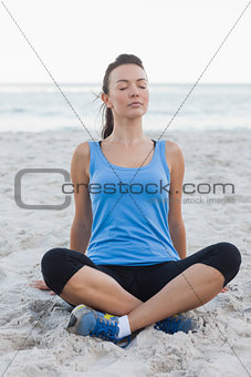 Sporty woman sitting in sand