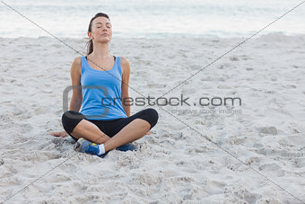 Brunette woman sitting after sport at beach