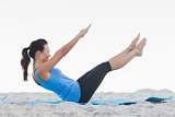 Woman doing pilates on exercise mat