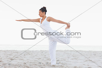 Brunette woman wearing all white stretching in yoga pose