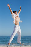 Attractive man jumping on beach