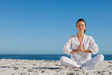 Peaceful woman practicing yoga on the beach