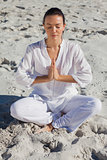 Concentrated woman practicing yoga on the beach