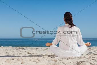 Woman doing yoga sitting back to camera