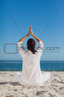 Brunette woman sitting back to camera practicing yoga