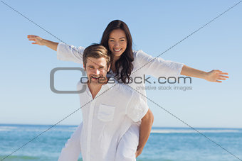 Woman sitting on mans back smiling at camera