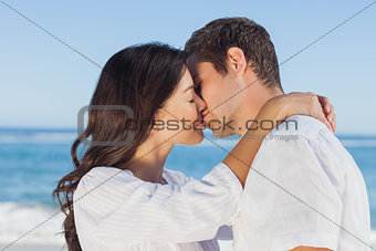 Couple embracing and kissing each other on the beach