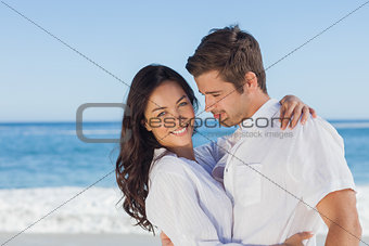 Young couple embracing and posing on the beach