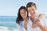 Cheerful couple embracing on the beach