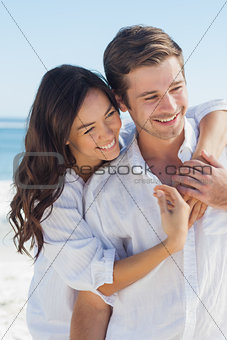 Smiling couple embracing each other on the beach